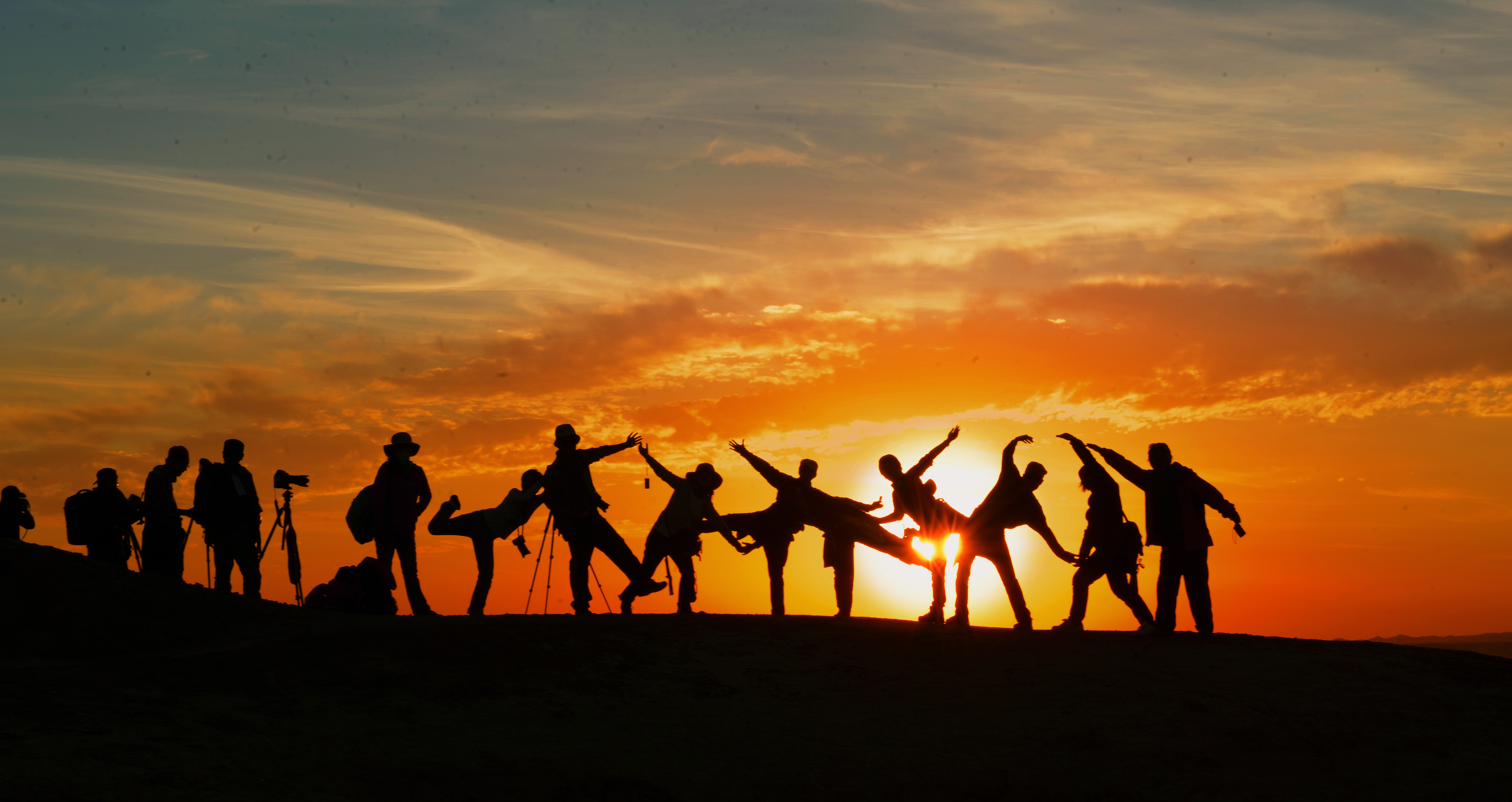 Mennesker poserer i silhuet mod solnedgangen.